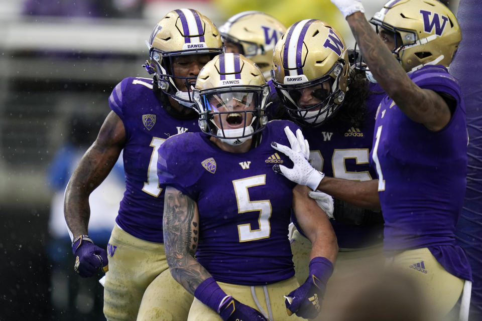 Washington running back Sean McGrew (5) celebrates his touchdown run against Arkansas State with teammates in the first half of an NCAA college football game, Saturday, Sept. 18, 2021, in Seattle. (AP Photo/Elaine Thompson)