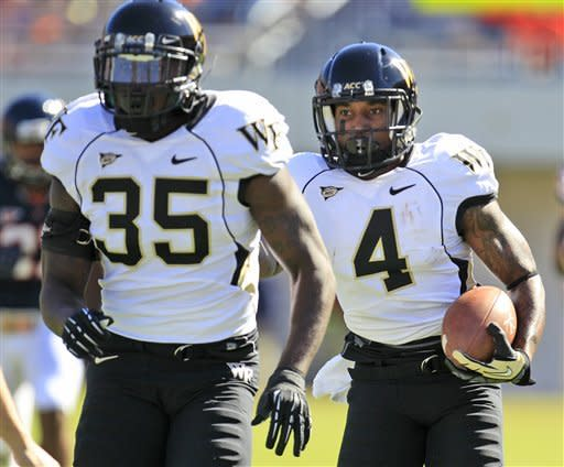Wake Forest linebacker Zachary Allen (35) leads wide receiver Lovell Jackson (4) downfield as he returns a punt during the first half of an NCAA college football game against Virginia at Scott Stadium in Charlottesville, Va., Saturday, Oct. 20, 2012. (AP Photo/Steve Helber)