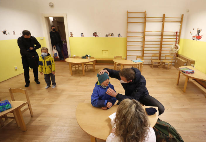 A young boy undergoes rapid COVID-19 test before entering his class at a kindergarden in Prague, Czech Republic, Monday, April 12, 2021. The Czech government has agreed to start easing the tight lockdown in one of the hardest-hit European countries and has given a green light for at least some children to return to schools. (AP Photo/Petr David Josek)