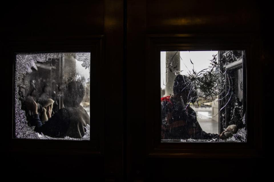workers clean broken glass on doors at us capitol