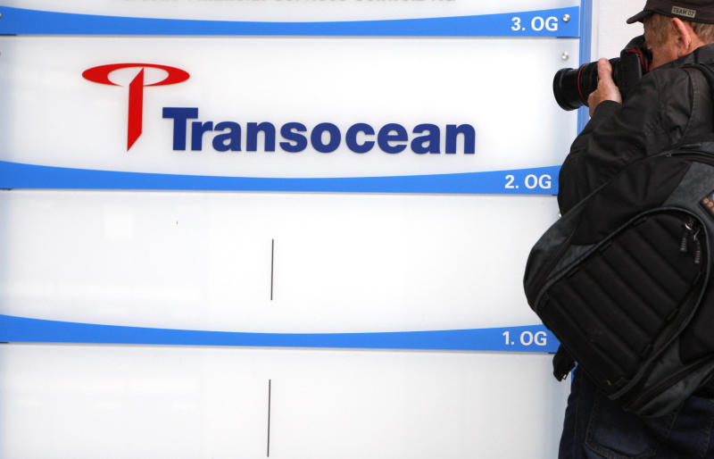 FILE - In this May 15, 2010 file photo a member of the press takes photographs of a company logo at the headquarters of the offshore drilling company Transocean in Steinhausen, Switzerland. Foreign executives who moved their company headquarters to Switzerland to get better tax deals for their firms may find themselves paying the price for it this weekend. A plan to crack down on excessive corporate pay packages is predicted to pass at the ballot box Sunday. (AP Photo/Keystone, Sigi Tischler, File)