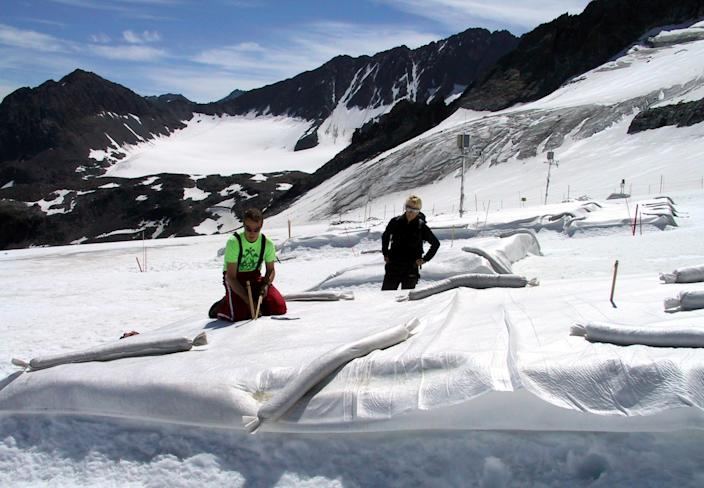 FILE - In this July 4, 2005 file photo Marc Olefs, left, and Andrea Fischer, researchers from the Innsbruck University check a field covered with white polyethylene against the backdrop of majestic jagged peaks at Eisgrat (Ice Spine) skiing station on Stubai glacier near the village of Neustift im Stubaital in the alpine Austrian province of Tyrol. It's Plan B in the fight against climate change: cooling the planet by sucking heat-trapping CO2 from the air or reflecting sunlight back into space. The U.N.'s expert panel on climate change is under pressure from both sides this week in Berlin, Germany, as it considers whether geoengineering should be part of the toolkit that governments use to keep global warming in check. (AP Photo/George Jahn, File)