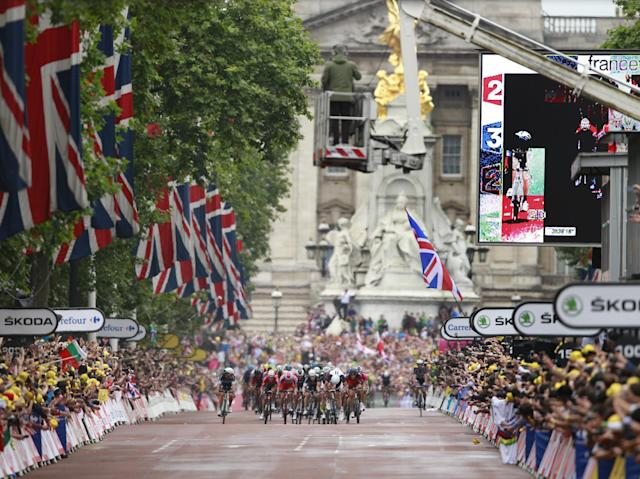 The pack with Stage winner Marcel Kittel of Germany sprints down The Mall as Buckingham Palace is seen in the rear during the third stage of the Tour de France cycling race over 155 kilometers (96.3 miles) with start in Cambridge and finish in London, England, Monday, July 7, 2014. (AP Photo/Peter Dejong)