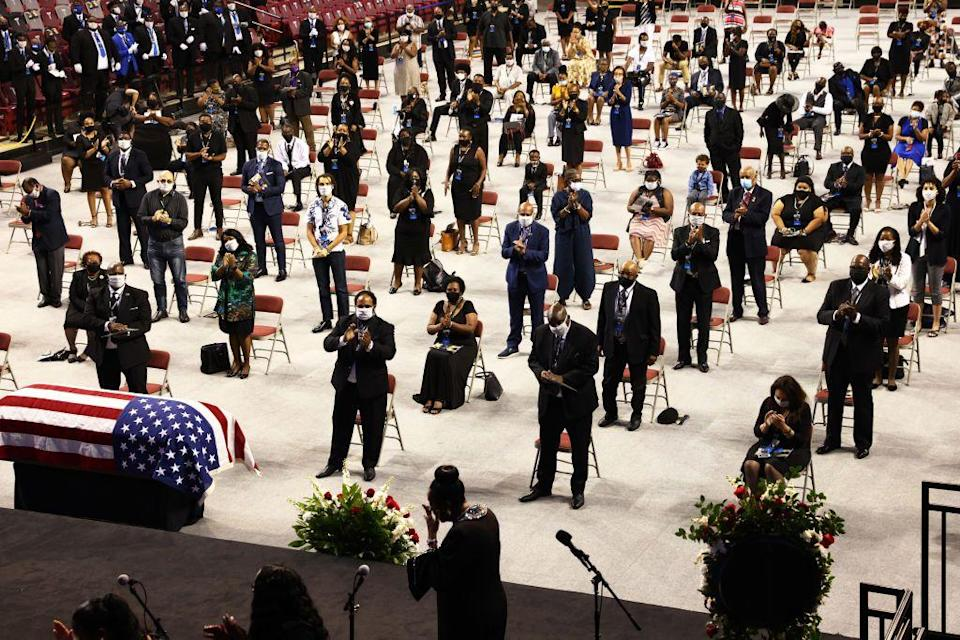 "<p>Attendees stood and clapped for Peoples during the ceremony. According to <em><a href=""https://abcnews.go.com/US/boy-troy-funeral-services-begin-late-rep-john/story?id=71985321"" rel=""nofollow noopener"" target=""_blank"" data-ylk=""slk:ABC News"" class=""link rapid-noclick-resp"">ABC News</a></em>, the funeral was conducted in ""homegoing"" style, ""a word used to describe African American funerals celebrating the life of the deceased which often includes heartfelt remembrances.""<br></p>"