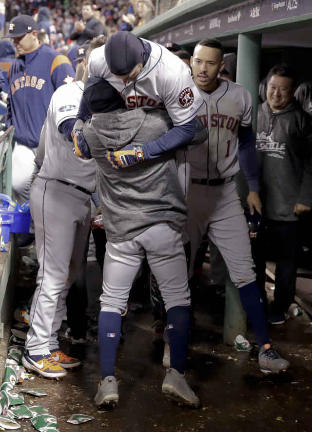 Houston Astros' Josh Reddick celebrates in the dugout after a home run during the ninth inning in Game 1 of a baseball American League Championship Series on Saturday, Oct. 13, 2018, in Boston. (AP Photo/David J. Phillip)