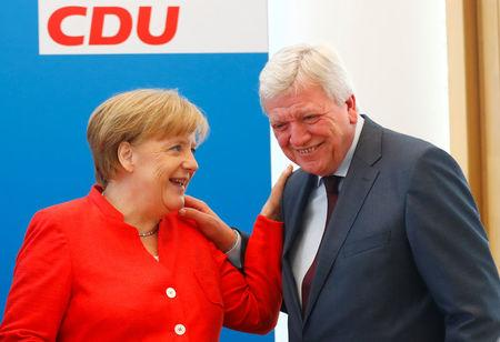 German Chancellor Angela Merkel and Volker Bouffier react as they attend the board meeting of Germany's Christian Democratic Union (CDU) in Berlin, Germany, June 18 2018. REUTERS/Hannibal Hanschke