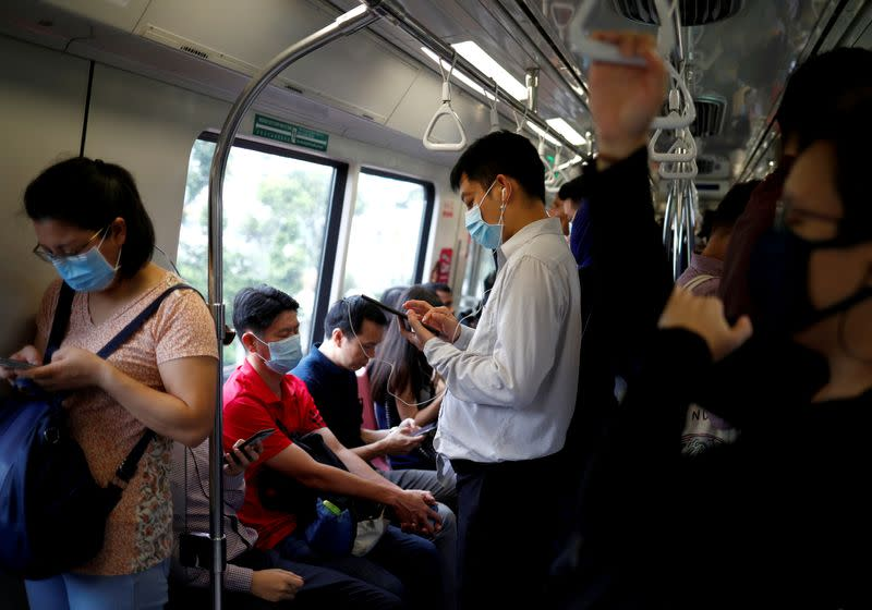 Commuters wearing masks in precaution of the coronavirus outbreak are pictured in a train during their morning commute in Singapore