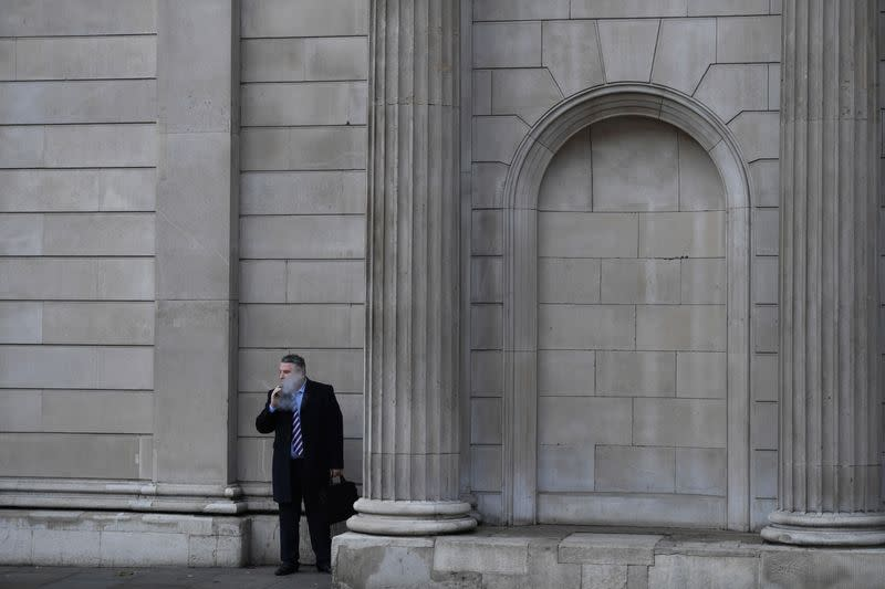 FILE PHOTO: A man smokes outside the Bank of England in the City of London