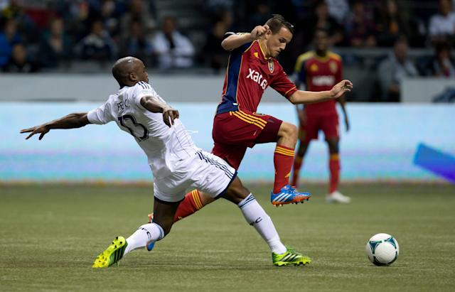 Real Salt Lake's Luis Gil, right, leaps over Vancouver Whitecaps' Nigel Reo-Coker, of England, to get to the ball during the first half of an MLS soccer game Saturday, Sept. 28, 2013, in Vancouver, British Columbia. (AP Photo/The Canadian Press, Darryl Dyck)