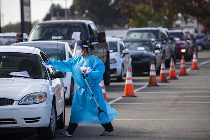 A 360 Clinic health care worker conducts testing at a drive-through site in Costa Mesa.