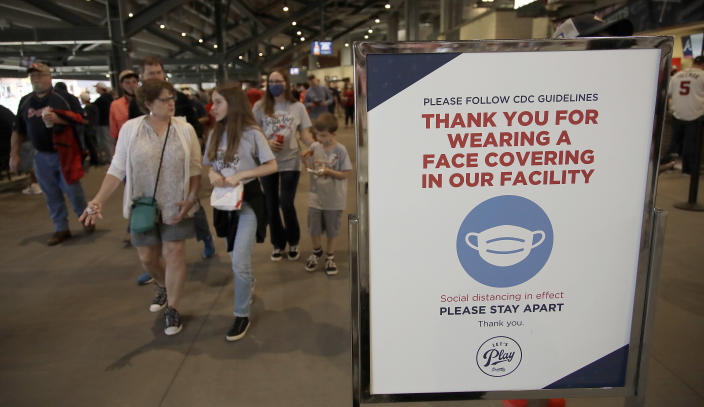 People make their way into Truist Park as they pass signage thanking fans for wearing a face mask per CDC guidelines prior to the baseball game between the Atlanta Braves and the Philadelphia Phillies on Saturday, May 8, 2021, in Atlanta. The Braves have opened the park to full attendance on the weekend for the first time in a year. (AP Photo/Ben Margot)