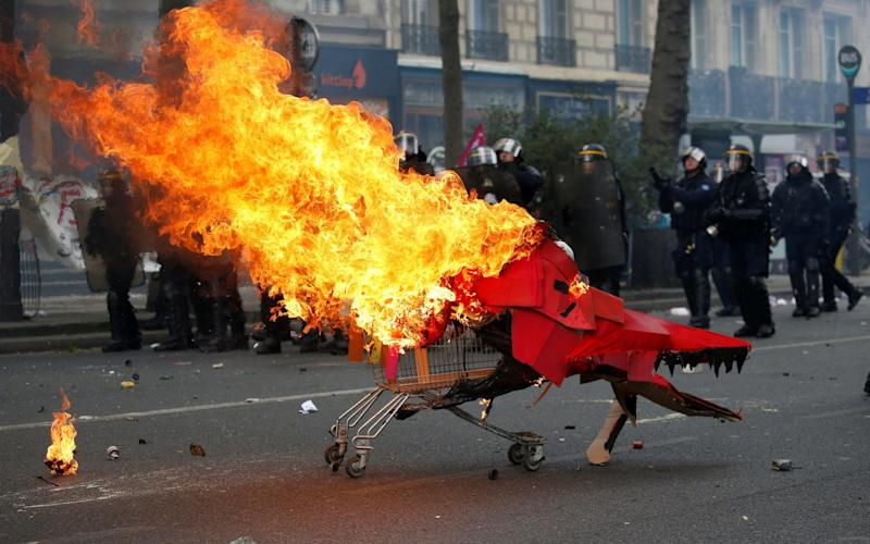Flames from a burning cardboard dragon in a caddy are seen near French CRS riot police - Credit: Reuters