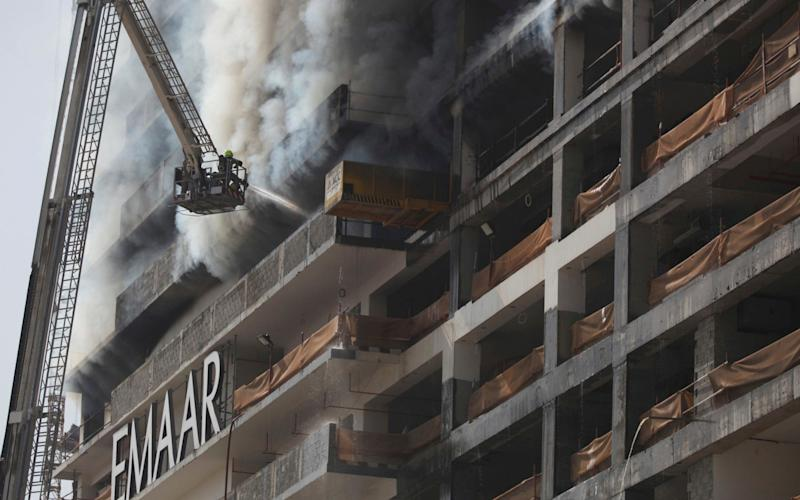 Flames licked out of the podium level of the building as firefighters battled the blaze - Credit:  Jon Gambrell/AP
