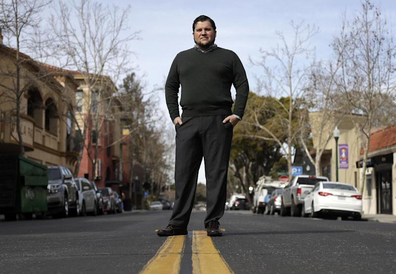 "In this Friday, March 3, 2017 photo, Michael Clark poses for a photo in downtown Campbell, Calif. Clark, a biotech executive, drew cheers after telling a gathering of anti-Trump activists that he'd closed his Wells Fargo account to protest the pipeline. Clark grew up in New Hampshire and then in Silicon Valley, when his mother took a job at Apple in the 1990s. He always considered himself a political independent, a moderate. But Trump's election horrified him and, with a friend who runs a gourmet chocolate shop, he founded a chapter of the national liberal group ""Indivisible"" in Campbell. (AP Photo/Marcio Jose Sanchez)"
