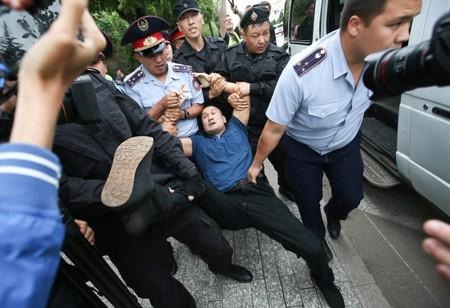 Police officers detain an opposition supporter during a protest against presidential election results, in Almaty