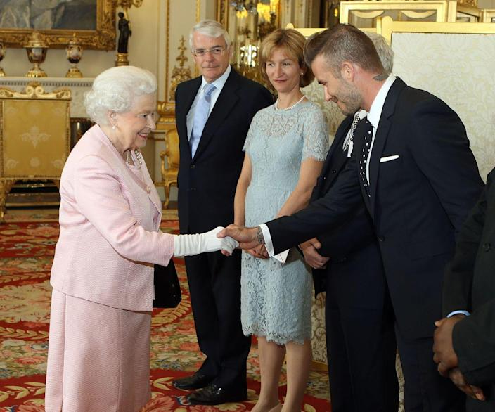 <p>Mr. Beckham first met the Queen in 2003 when he received an OBE. Over a decade later, in 2015, the soccer star opted for a black and white polka dot tie and suit to hang with her Majesty at Buckingham Palace for a reception of the Queen's Young Leaders program. </p>