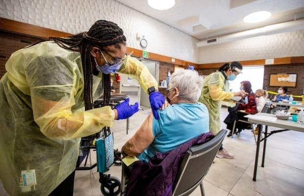 Nurse Tahani McDonald from Humber River Hospital administers the Moderna vaccine at a Toronto Community Housing seniors building on March 25, 2021.  (Carlos Osorio/Reuters - image credit)
