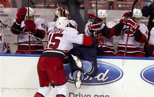 The Carolina Hurricanes bench dodges as Hurricane player Tuomo Ruufu (15) and Florida Panthers' Tomas Fleischmann almost go into the area during the second period of an NHL hockey game in Sunrise, Fla., Sunday, March 11, 2012. (AP Photo/J Pat Carter)