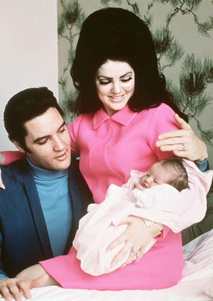 <p>Priscilla wears a hot pink dress and wraps her daughter, Lisa Marie Presley, in a light pink blanket as she and her husband, Elvis, prepare to leave the hospital in 1968. </p>