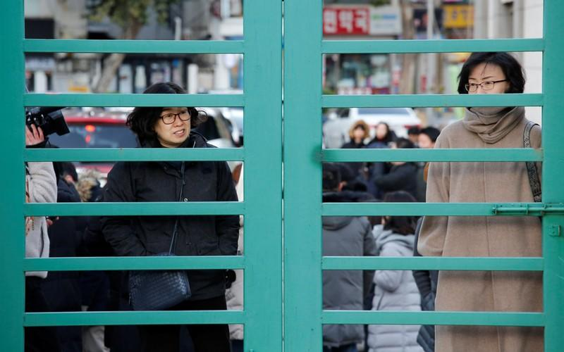 Mothers stand outside an entrance as their children get to the venue for taking the annual college entrance examinations, in front of an exam hall in Seoul