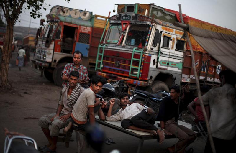 Indian truck drivers rest next to their parked trucks during a strike on the outskirts of New Delhi, India, Thursday, Sept. 20, 2012. Angry opposition workers have disrupted train services as part of a daylong strike in India to protest rising diesel prices and the government's decision to open the country's huge retail market to foreign companies. (AP Photo/Altaf Qadri)