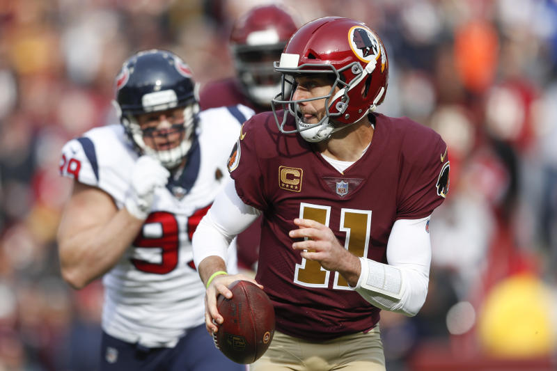 Washington Redskins quarterback Alex Smith (11) scrambles past Houston Texans defensive end J.J. Watt (99) during the first half of an NFL football game, Sunday, Nov. 18, 2018, in Landover, Md. (AP Photo/Pablo Martinez Monsivais)