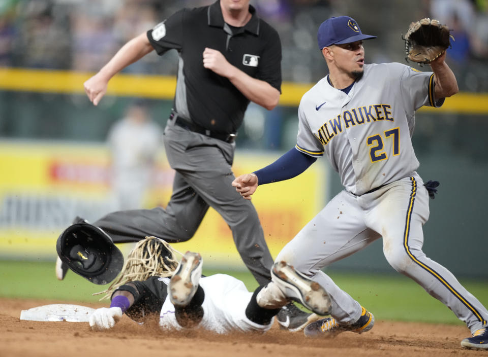 Milwaukee Brewers shortstop Willy Adames, right, looks for the throw as Colorado Rockies' Raimel Tapia, bottom left, slides safely into second base with an RBI-double in the sixth inning of a baseball game Thursday, June 17, 2021, in Denver. (AP Photo/David Zalubowski)