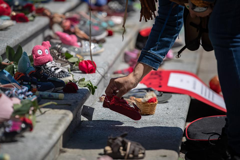 <p>A woman places one of 215 pairs of children's shoes on the steps of the Vancouver Art Gallery as a memorial to the 215 children whose remains have been found buried at the site of a former residential school in Kamloops, in Vancouver, on Friday, May 28, 2021. Chief Rosanne Casimir of the Tk'emlups te Secwépemc First Nation said in a news release Thursday that the remains were confirmed last weekend with the help of a ground-penetrating radar specialist. THE CANADIAN PRESS/Darryl Dyck</p>
