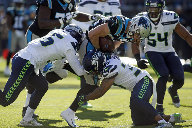 Seattle Seahawks cornerback Akeem King, left, and defensive back Quandre Diggs (37) tackle Carolina Panthers running back Christian McCaffrey (22) during the first half of an NFL football game in Charlotte, N.C., Sunday, Dec. 15, 2019. (AP Photo/Brian Blanco)