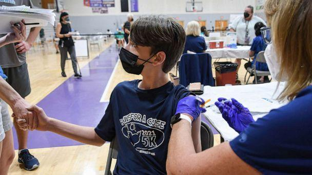 PHOTO: A 12 year old boy holds his mother's hand while a nurse gives him a shot of the Pfizer COVID-19 vaccine at a vaccination clinic at Winter Springs High School, on Sept. 11, 2021, in Winter Springs, Fla. (Paul Hennessy/SOPA Images via ZUMA Wire via Newscom)