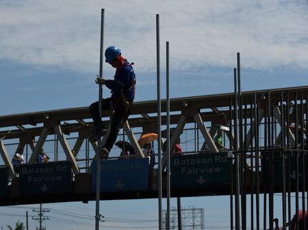 A worker assembles a pole at a construction site of the Metro Rail Transit (MRT) on Commonwealth Avenue in Quezon City, metro Manila, May 23, 2018. REUTERS/Dondi Tawatao