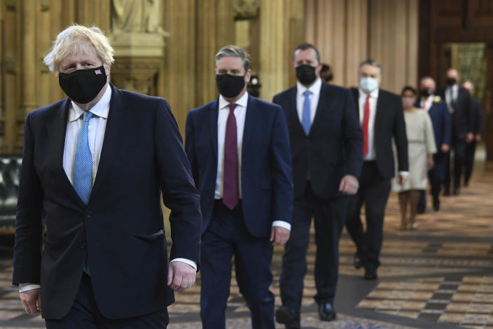 Britain's Prime Minister Boris Johnson, left, and Labour Party leader Keir Starmer, second left, walk through the Central Lobby on the way to the House of Lords prior to Queen Elizabeth II delivering a speech during the State Opening of Parliament in the House of Lords at the Palace of Westminster in London, Tuesday May 11, 2021. (Stefan Rousseau/Pool via AP)