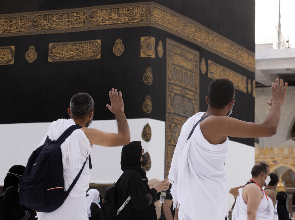 Muslim pilgrims pray in front of the Kaaba, the cubic building at the Grand Mosque, as they wear masks and keep social distancing, a day before the annual hajj pilgrimage, Saturday, July 17, 2021. The pilgrimage to Mecca required once in a lifetime of every Muslim who can afford it and is physically able to make it, used to draw more than 2 million people. But for a second straight year it has been curtailed due to the coronavirus with only vaccinated people in Saudi Arabia able to participate. (AP Photo/Amr Nabil)