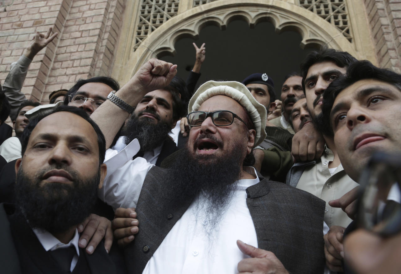 <p> Hafiz Saeed, head of the Pakistani religious party, Jamaat-ud-Dawa, gestures outside a court in Lahore, Pakistan, Wednesday, Nov. 22, 2017. The court rejected the government's plea to extend for three months the house arrest of Saeed, the former leader of a banned militant group allegedly linked to 2008 Mumbai terrorist attack. (AP Photo/K.M. Chaudary) </p>