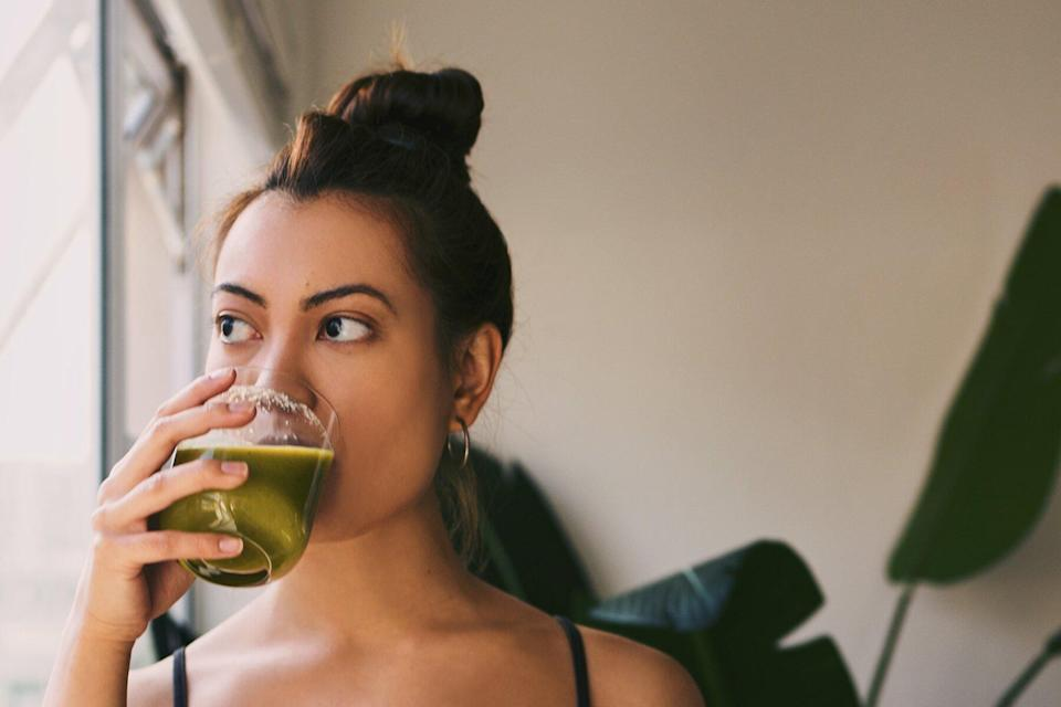 Woman drinking a green juice at home
