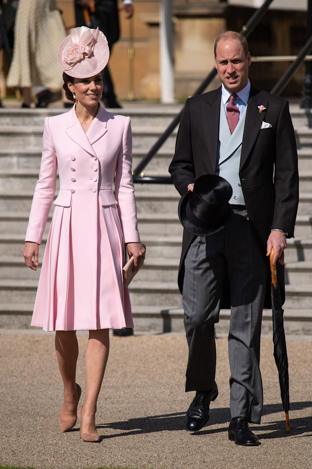 The Duke and Duchess of Cambridge at a Buckingham Palace garden party. Kate wore a pink Alexander McQueen coat dress with a matching hat by Juliette Botterill, her Gianvito Rossi praline pumps and her Loeffler Randall clutch. She accessorised with Princess Diana's Collingwood pearl earrings. [Photo: PA]