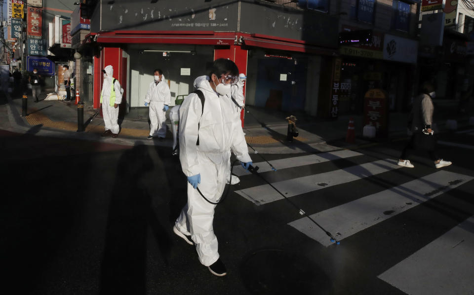 Workers in protective gear spray disinfectant to help curb the spread of the coronavirus in Seoul, South Korea, Tuesday, Oct. 6, 2020. (AP Photo/Lee Jin-man)