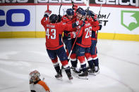 Washington Capitals right wing Tom Wilson (43), center Nic Dowd (26) and others celebrate after an NHL hockey game as Philadelphia Flyers goaltender Alex Lyon, bottom, skates away Saturday, May 8, 2021, in Washington. The Capitals won 2-1 in overtime. (AP Photo/Nick Wass)
