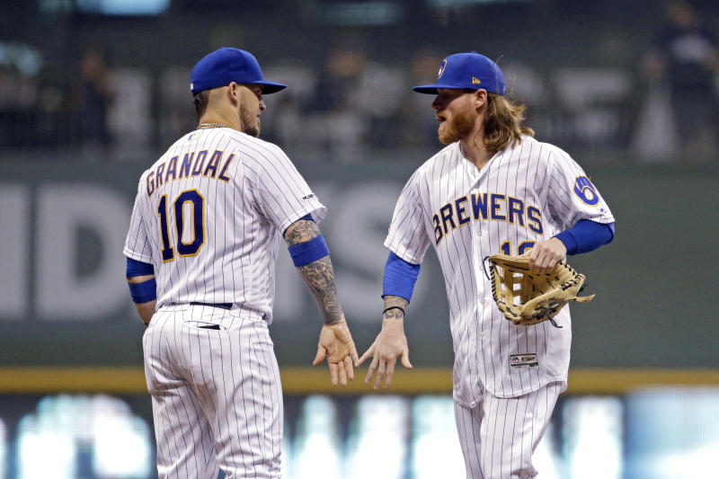 Milwaukee Brewers' Ben Gamel, right, and Yasmani Grandal congratulate one another after the team's baseball game against the Pittsburgh Pirates on Friday, Sept. 20, 2019, in Milwaukee. The Brewers won 10-1. (AP Photo/Aaron Gash)