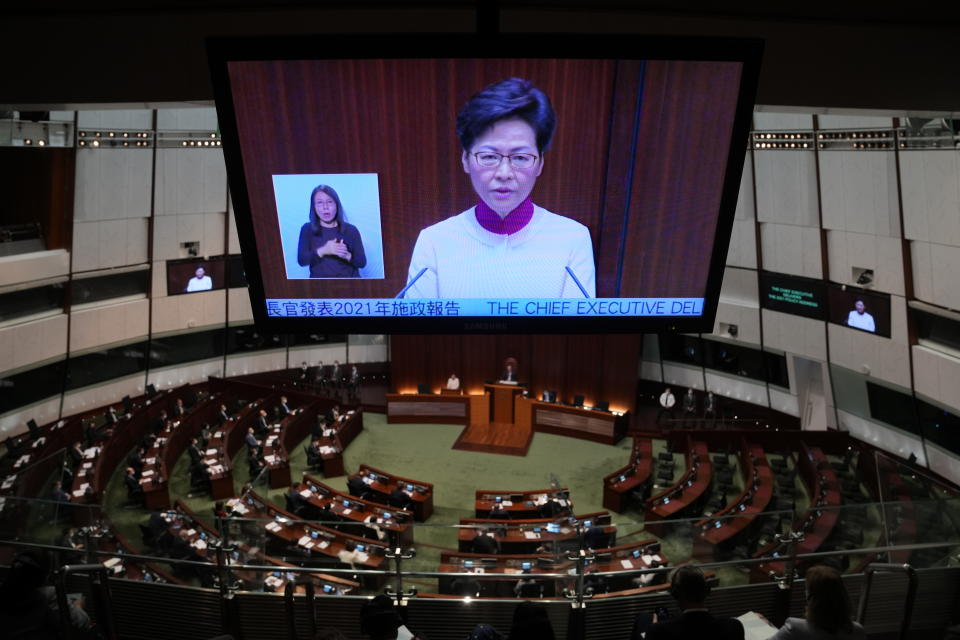 A TV screen shows Hong Kong Chief Executive Carrie Lam delivering her policies at the chamber of Legislative Council in Hong Kong, Wednesday, Oct. 6, 2021. Lam announced a major development plan Wednesday for Hong Kong's border area with mainland China in the last annual policy address of her current term. (AP Photo/Kin Cheung)
