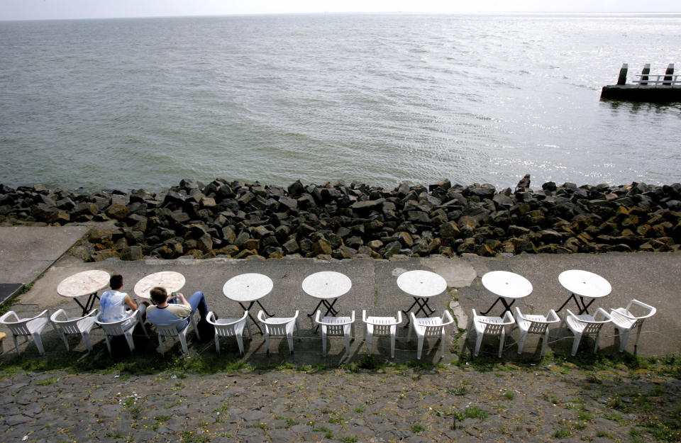 In this image taken Thursday Sept. 1, 2005, Tourists enjoy a bit of sun as they sit on Afsluitdijk, one of the dikes protecting the Dutch heartland, near the north western town of Den Oever, Netherlands. Rising in a thin line through the surface of waters separating the provinces of North Holland and Friesland, the 87-year-old Afsluitdijk is one of the low-lying Netherlands' key defenses against the sea. With climate change bringing more powerful storms and rising sea levels, it's getting a major makeover. (AP Photo/Peter Dejong)
