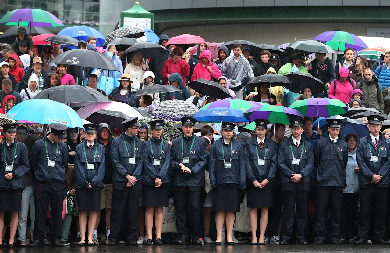 LONDON, ENGLAND - JUNE 28: Security staff wait with spectators for the opening of the gates at the Wimbledon Lawn Tennis Championships on June 28, 2013 in London, England. Rain has delayed play on the outside courts today on day five of the tournament. (Photo by Peter Macdiarmid/Getty Images)