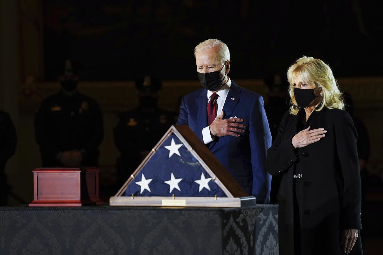 President Joe Biden and first lady Jill Biden pay their respects to the late U.S. Capitol Police officer Brian Sicknick as an urn with his cremated remains lies in honor on a black-draped table at center of Capitol Rotunda, Tuesday, Feb. 2, 2021, in Washington. (Erin Schaff/The New York Times via AP, Pool)