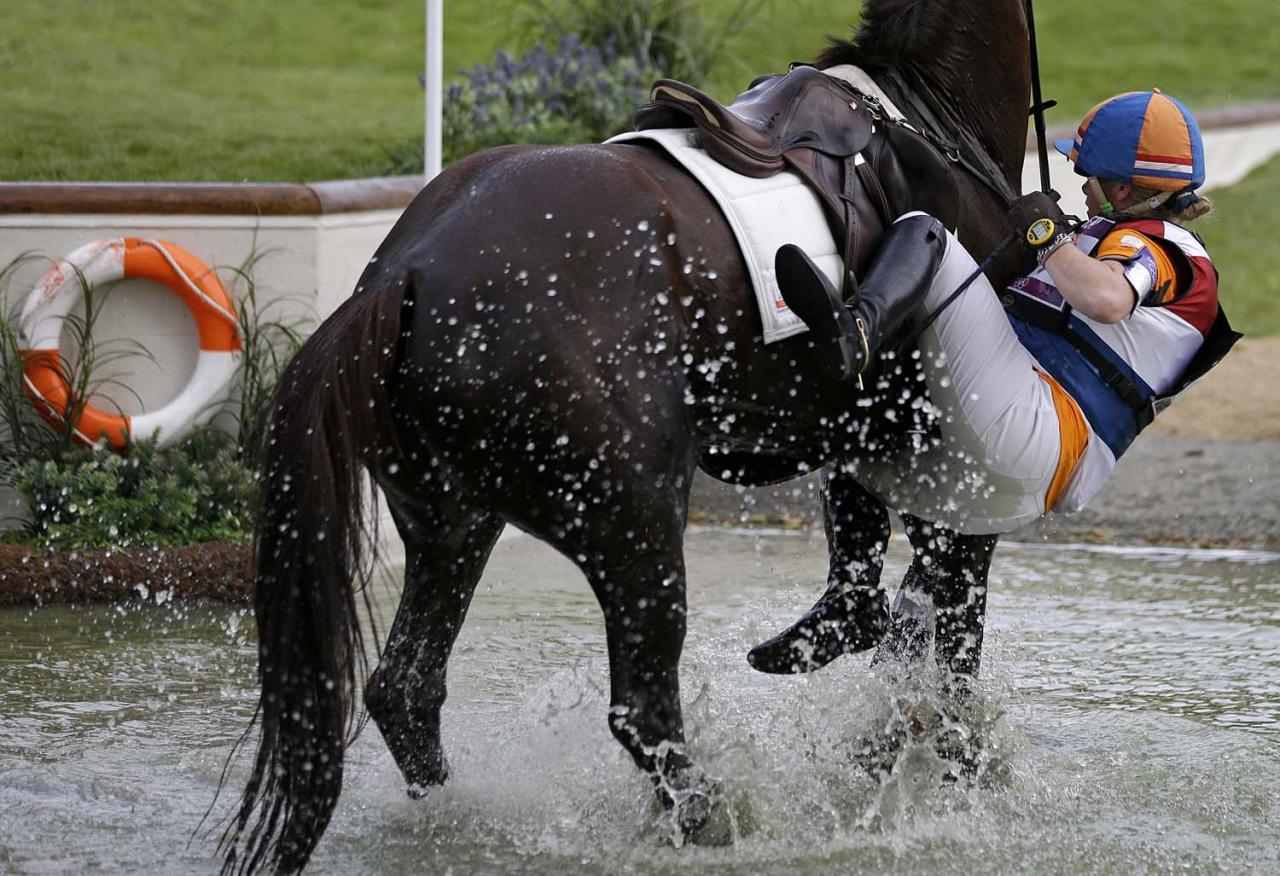Elaine Pen, of the Netherlands, falls off her horse Vira, resulting in a disqualification while competing in the equestrian eventing cross country phase at the 2012 Summer Olympics, Monday, July 30, 2012, in London. (AP Photo/David Goldman)