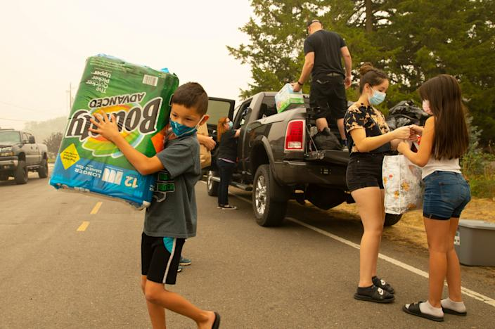 Josue Alvarez, 8, carries a large package of paper towels donated to his family by staff at the Medford, Ore., hospital where his mother Noemi Alvarez works. The community has come together to help the family this week after their home was lost to the Almeda Fire.