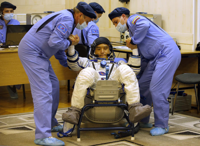 <p>Russian Space Agency experts help Japanese astronaut Takuya Onishi, member of the main crew to the International Space Station (ISS), to stand up after inspecting his space suit prior to the launch of Soyuz-FG rocket at the Russian leased Baikonur cosmodrome, Kazakhstan, Thursday, July 7, 2016. (AP Photo/Dmitri Lovetsky) </p>