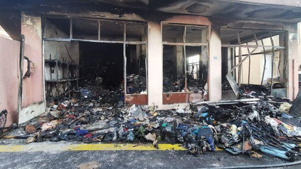 PHOTO: Destroyed donated supplies for migrants spill out from the 'Solidarity Warehouse' in Chios, Greece, after an apparent arson attack. (One Family - No Borders)