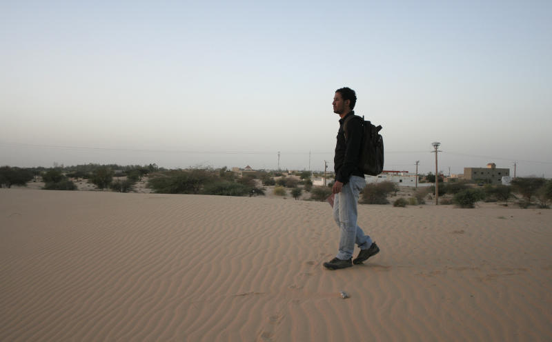 In this image taken on Saturday Feb. 2, 2013, Baba Ahmed, 26, AP's correspondent in Bamako, walks on the sand dunes near his neighborhood in Timbuktu, Mali where his used to picnic with friends when he was in high school in Timbuktu between 2003 and 2005. In Baba Ahmed's own words, not a single light could be seen in my hometown of Timbuktu as we approached it at night just days after it was liberated from the al-Qaida-linked militants who ruled for nearly 10 months. The last time Baba had visited was in May, a month after the Islamic rebels seized Timbuktu. After my visit I covered my hometown's plight for The Associated Press from the distant capital of Bamako, straining for information over the telephone each week about what had become of this city I love. (AP Photo/Harouna Traore)