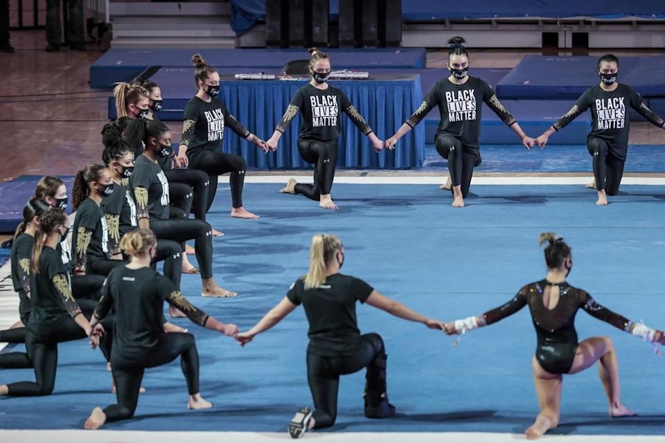 UCLA gymnasts join hands during a prematch ceremony.