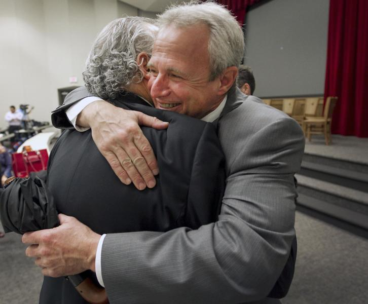 Michael Morton, hugs defense attorney Jerry Goldstein, after speaking to the public for the first time since he was freed from prison, Thursday, March 29, 2012 in Austin, Texas. Morton, who spent nearly 25 years behind bars for a murder he didn't commit is fighting for tougher penalties targeting prosecutors who withhold evidence, saying he wants to prevent other innocent people from overzealous prosecutors/losing years of their life. (AP Photo/Austin American-Statesman, Ralph Barrera) MAGS OUT; NO SALES; INTERNET AND TV MUST CREDIT PHOTOGRAPHER AND STATESMAN.COM